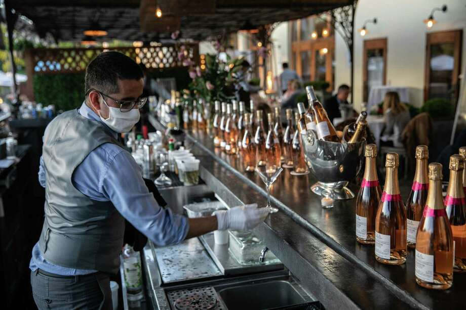A bartender serves drinks at L'escale restaurant on May 20, 2020 in Greenwich, Connecticut. After two months of closures due to the coronavirus pandemic, Connecticut partially reopened businesses on May 20, one of the last states to do so. (Photo by John Moore/Getty Images) Photo: John Moore / Getty Images / 2020 Getty Images