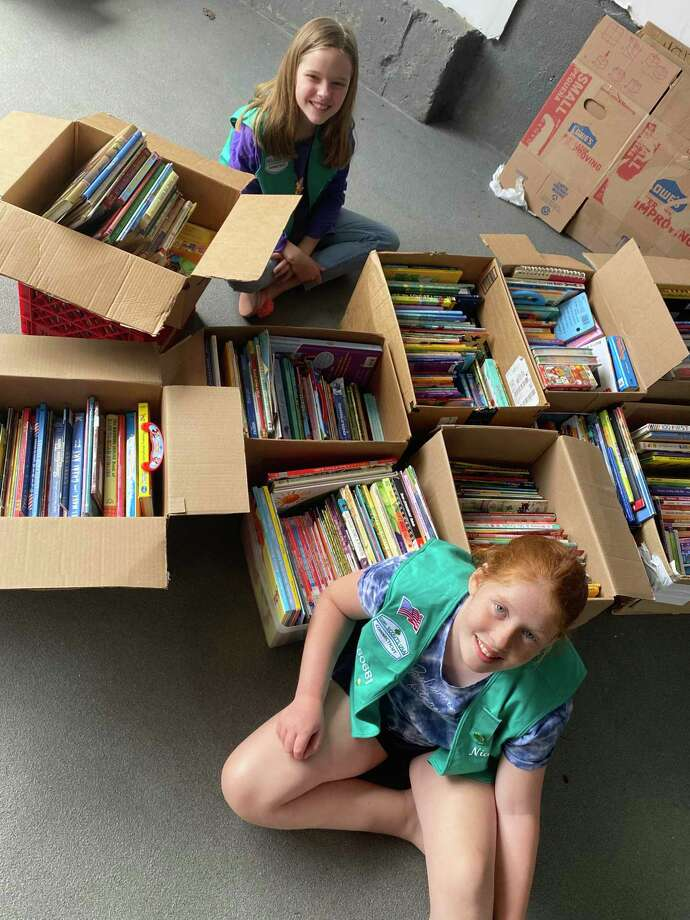 Girl Scouts Jocelyn O'Neil and Niamh O'Donovan organize the books from the book drive. Photo: Contributed /