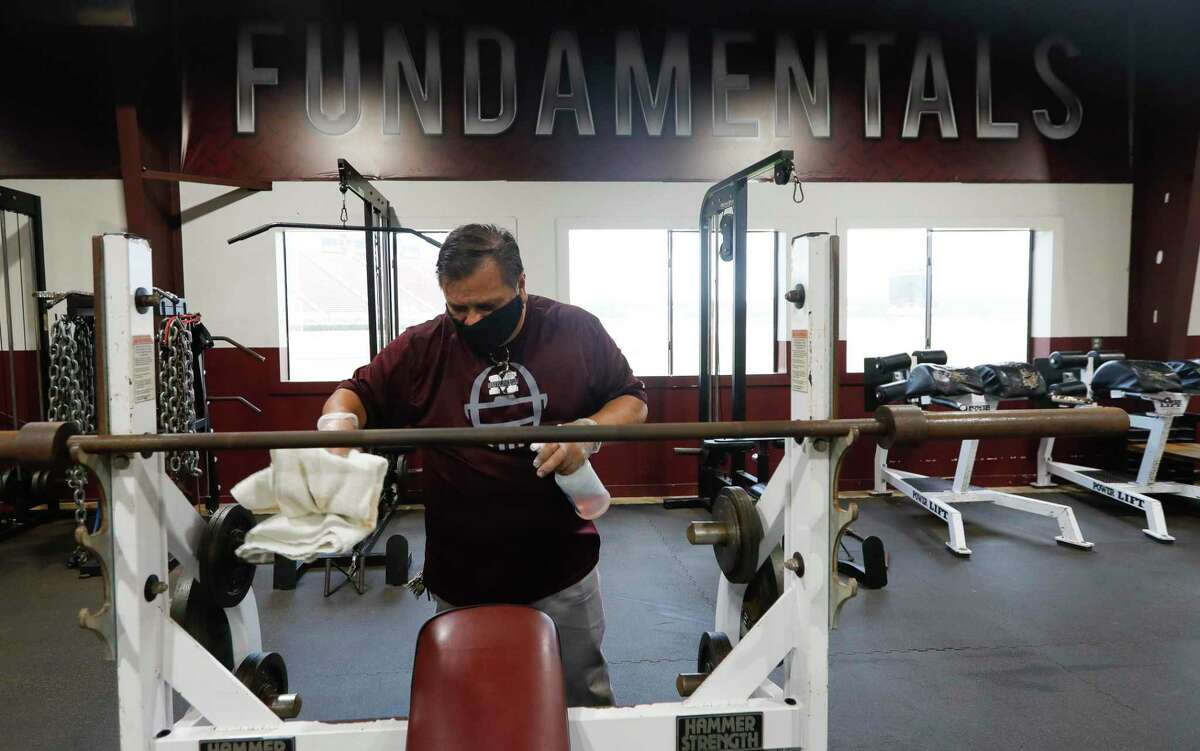 Custodian Phillip Ramirez helps clean and sanitize the weight room at Magnolia High School, Tuesday, June 2, 2020, in Magnolia. UIL schools are allowed to open strength and conditioning sessions to athletes starting Monday, June 8, under social distancing and other safety guidelines.