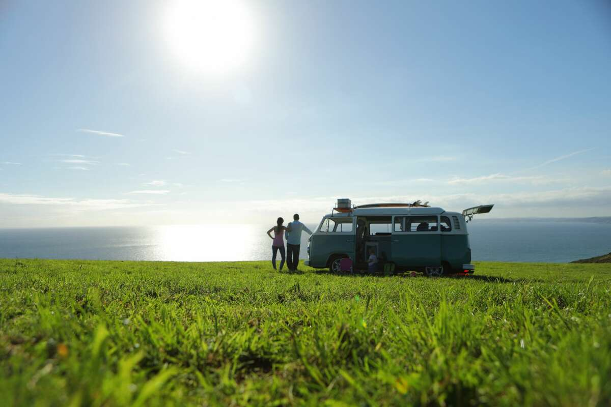 Family with camper in field looking at sea.