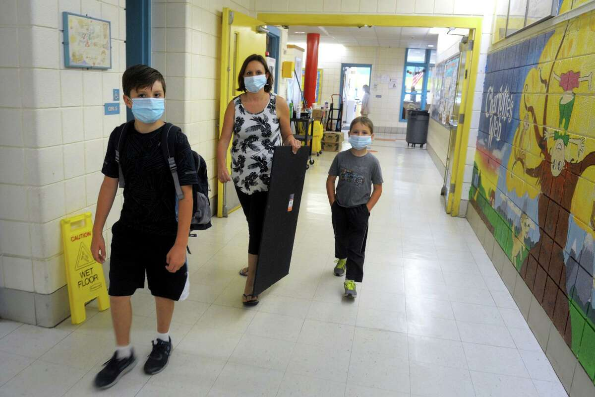 Kirsten Betts walks with her sons Jackson and Wyatt in a hallway at Sunnyside School, in Shelton, Conn. May 18, 2020. Shelton elementary schools were opened Monday so students could retrieve their personal belonging.