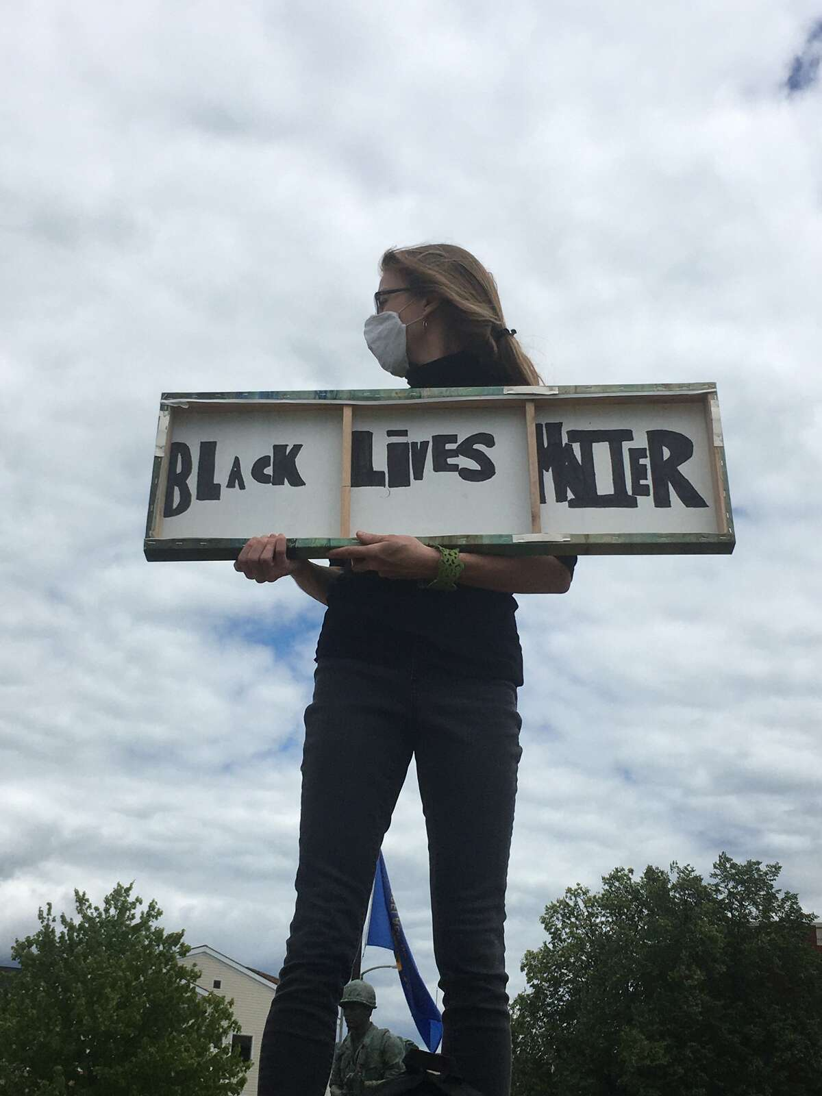 A demonstrator stands at the rally Sunday in Troy's Riverfront Park to protest the killings of men and women by police.