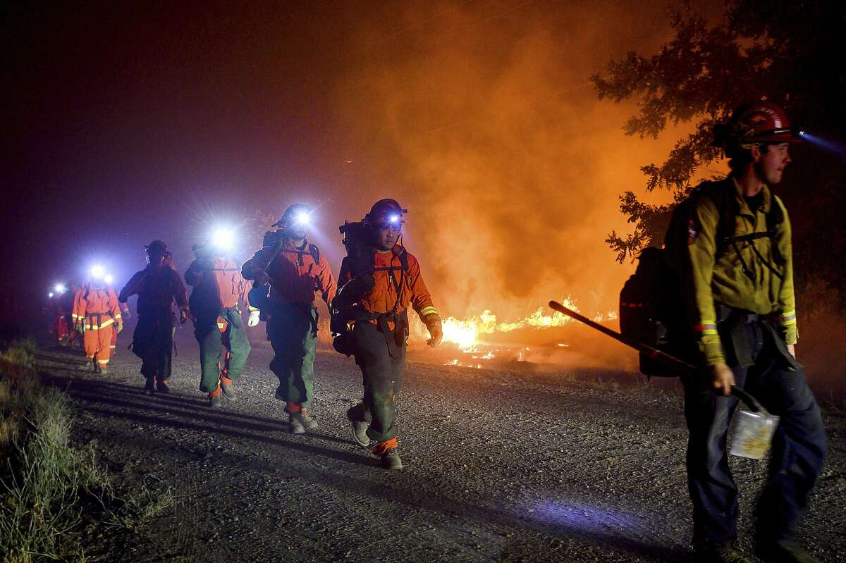 Inmate firefighters, left, battle the Quail Fire burning near Winters, Calif., on Sunday, June 7, 2020. (AP Photo/Noah Berger)