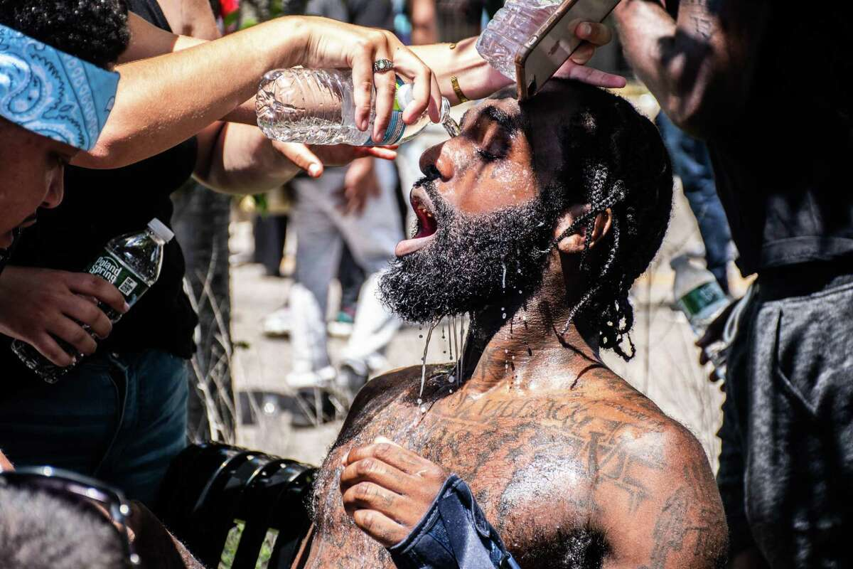 Protesters wash pepper spray of the eyes of Joe Grits, center, in Bridgeport, Connecticut Saturday, May 30.