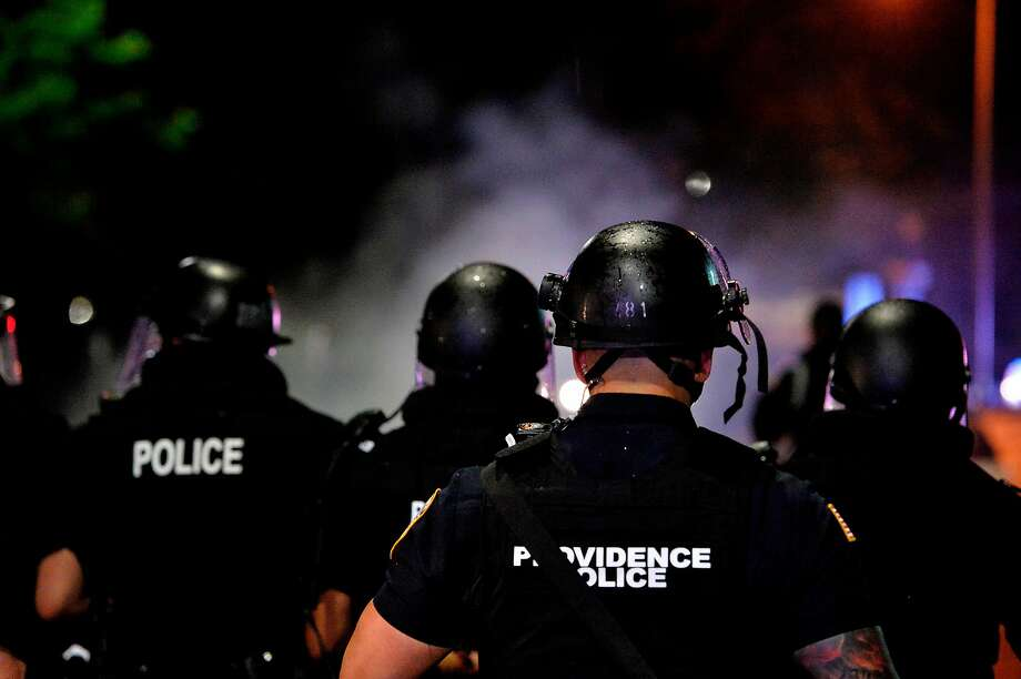 Police officers and National Guard soldiers make their way through a smoke filled street as they chase and confront protesters after curfew and after a peaceful Black Lives Matter rally in Providence, Rhode Island on June 5, 2020. (Photo by Joseph Prezioso / AFP) (Photo by JOSEPH PREZIOSO/AFP via Getty Images) Photo: Joseph Prezioso, AFP Via Getty Images