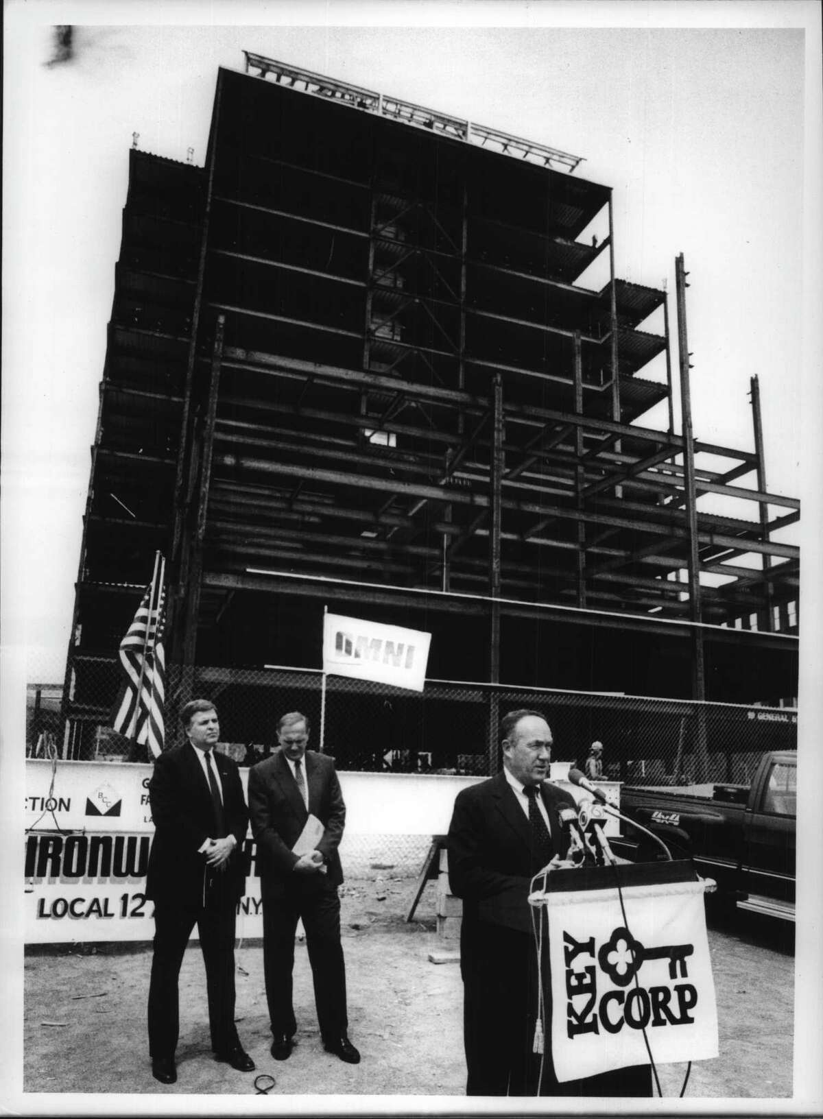 Mayor Thomas Whalen speaks at ceremony as Robert Curley, president and CEO for Key Bank of Eastern New York, and Richard D Lipps, Chairman Omni Development Company watch. The new Keycorp Building is under construction in the background on Hudson and South Pearl Street, Albany, New York. June 8, 1990 (Paul D. Kniskern Sr./Times Union Archive)