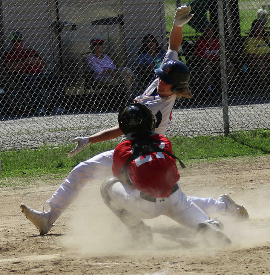 Alton's John Durrwachter (back) cannot elude the tag from Highland's catcher and is out on a play at the plate in the first game of a doubleheader Sunday at P.I.C. Park in Pierron. Photo: Greg Shashack / The Telegraph