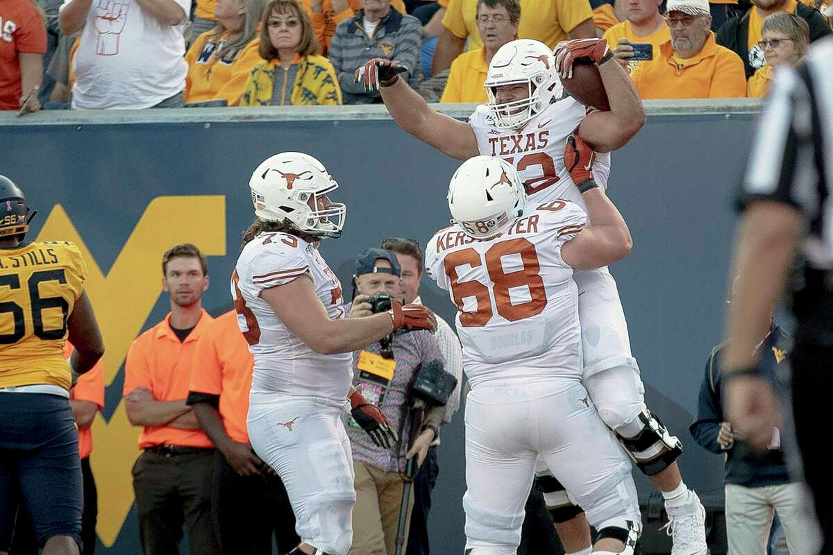 FILE - In this Oct. 5, 2019, file photo, Texas offensive lineman Samuel Cosmi (52) celebrates a touchdown against West Virginia during an NCAA college football game in Morgantown, W. Va. Cosmi lived every offensive lineman's dream when he caught a lateral from Sam Ehlinger and rumbled 12 yards for a touchdown in a 42-31 win over West Virginia. (Nick Wagner/Austin American-Statesman via AP, File)