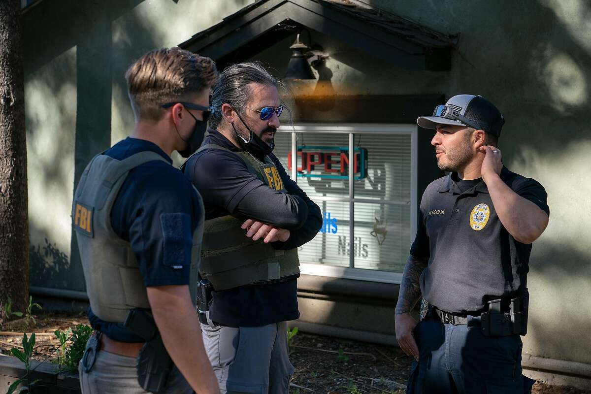 At left, FBI agents speaks to a a Santa Clara County Police Inspector, right, outside the Redwood Coast Dispensary where murder suspect Steven Carrillo attempted to carjack a car to escape authorities on Sunday, June 7, 2020 in Ben Lomond, Calif. Carrillo is suspected of killing Santa Cruz County Sheriff's deputy Damon Gutzwiller.