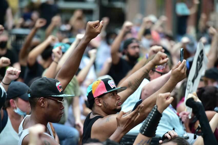 Marchers raise their fists during a vigil for Charles