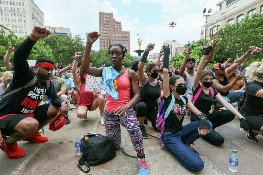Protesters kneel in a moment of silence in front of the Bexar County Courthouse on Sunday. Photo: Marvin Pfeiffer /Staff Photographer / **MANDATORY CREDIT FOR PHOTOG AND SAN ANTONIO EXPRESS-NEWS/NO SALES/MAGS OUT/TV