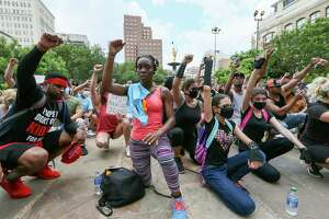 Protesters kneel in a moment of silence in front of the Bexar County Courthouse on Sunday.