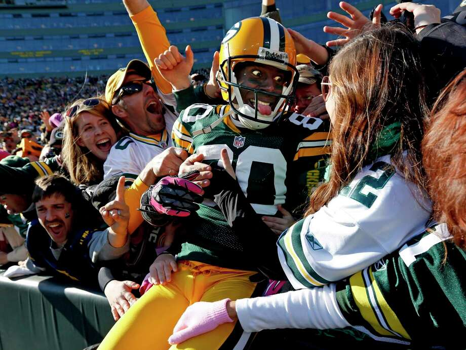 FILE - In this Oct. 28, 2012, file photo, Green Bay Packers wide receiver Donald Driver celebrates a touchdown after doing a Lambeau Leap during the second half of an NFL football game against the Jacksonville Jaguars, in Green Bay, Wisc. As lock-downs are lifted, restrictions on social gatherings eased and life begins to resemble some sense, sports are finally starting to emerge from the coronavirus pandemic. Many sports business experts believe those hardy fans will be the first to return. (AP Photo/Mike Roemer, File) / FR155603 AP