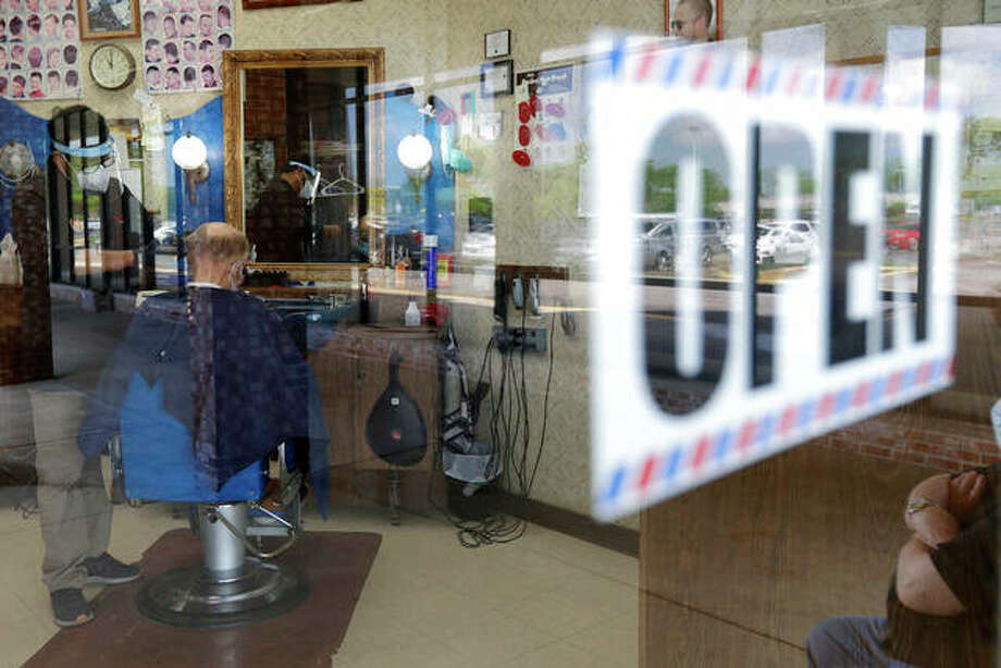 A barber wears a face mask and protective shield gives a client a haircut. More businesses were allowed to reopen May 29 and people started gathering in small groups while social distancing. Personal care services such as salons, spas and tattoo parlors have also reopened for reservations only. Photo: Nam Y. Huh | AP