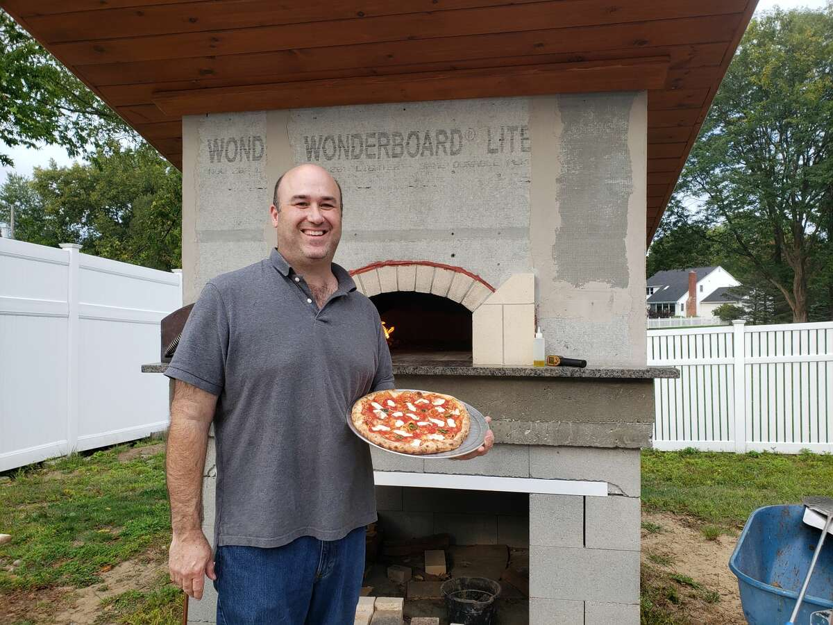 Jon Kunin and his at-home outdoor oven, in which he makes pizzas for his family and friends.