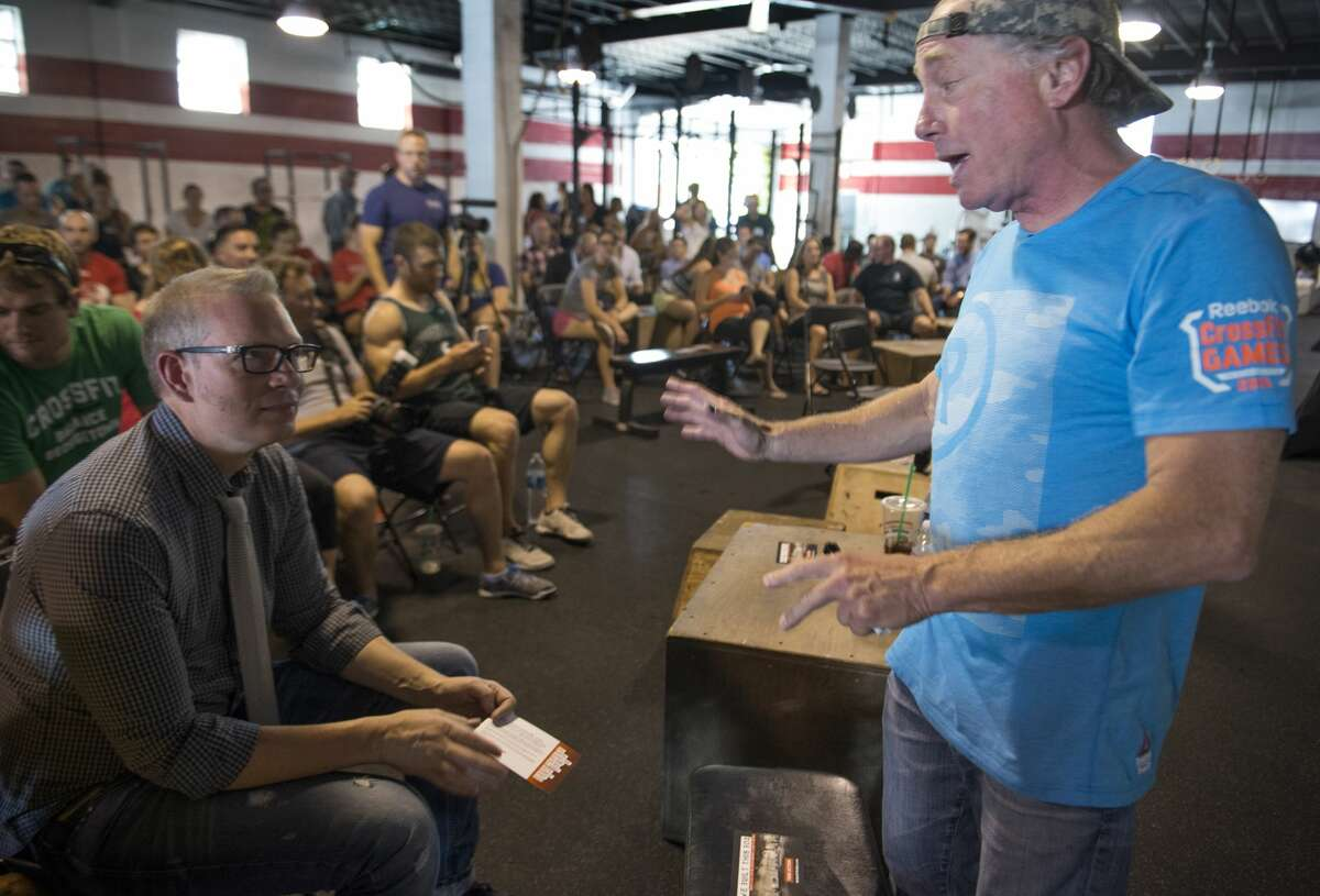 Crossfit Inc. founder and CEO Greg Glassman (right) talks to employees prior to a presentation at the Half street location in Washington, DC on July 31, 2015. Glassman received criticism for a tweet about the coronavirus pandemic and George Floyd.