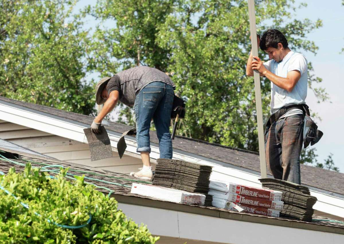 Roofing crews repair roofs around Midland 05/15/19 like these on a home on Fannin Ave. Tim Fischer/Reporter-Telegram