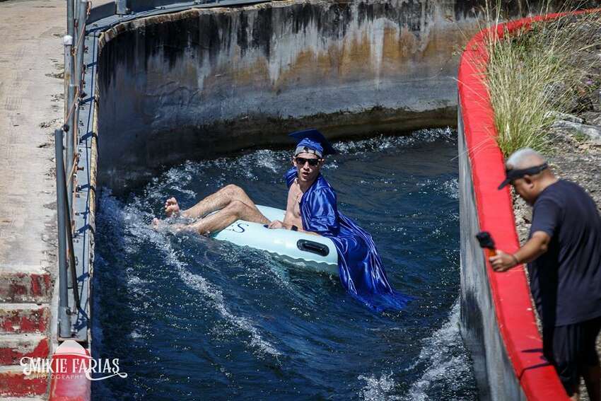 New Braunfels photographer Mikie Farias organized a photo shoot on the Comal River chute on June 6 for new graduates. The teens from New Braunfels High School showed up wearing their caps and gowns over their swimsuits.