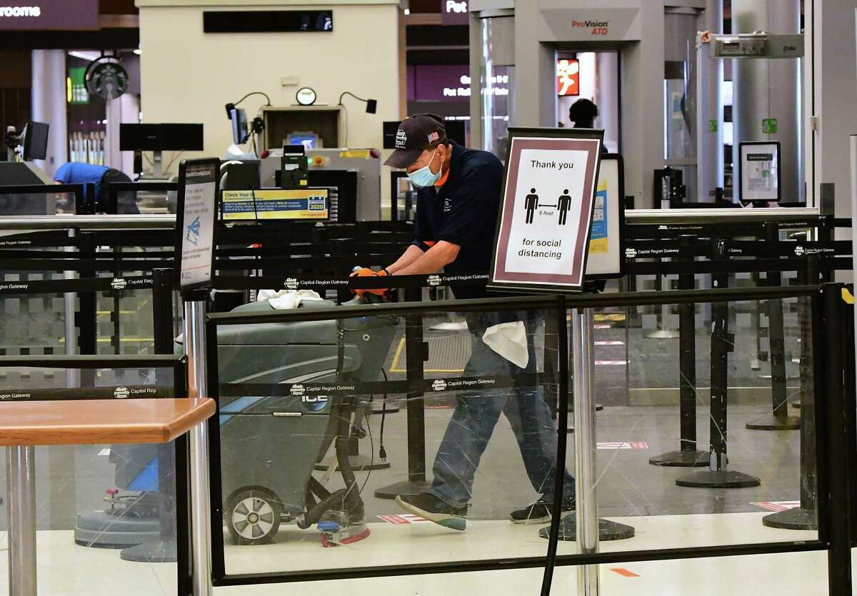 Leon Zayas disinfects the floor in the TSA checkpoint area at the Albany International Airport on Monday, June 8, 2020 in Colonie, N.Y. New technology introduced in recent weeks is intended to limit