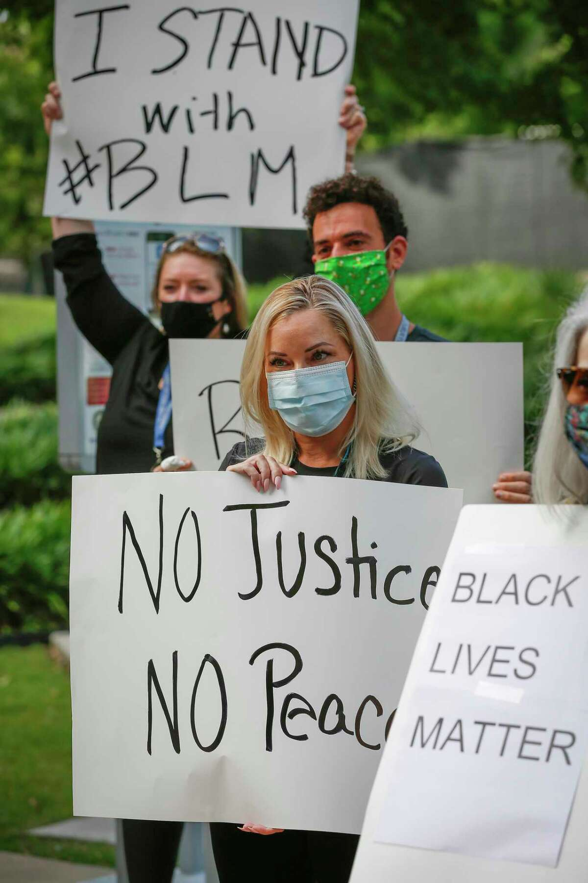 Mary Ruden holds a sign as she joined other Harris County Public Defenders as they gathered in support of black lives matter across from the Harris County Criminal Justice Center Monday, June 8, 2020, in Houston.
