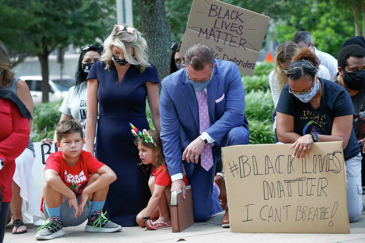 Baron Thiessen, 8 (left-right), his mother Taly, sister Berkley, 6, father Mark and Tanya Kelley take a knee to acknowledge the amount of time that Derek Chauvin kneeled into the neck of George Floyd as they joined other Harris County Public Defenders, family and friends in support of black lives matter across from the Harris County Criminal Justice Center Monday, June 8, 2020, in Houston.