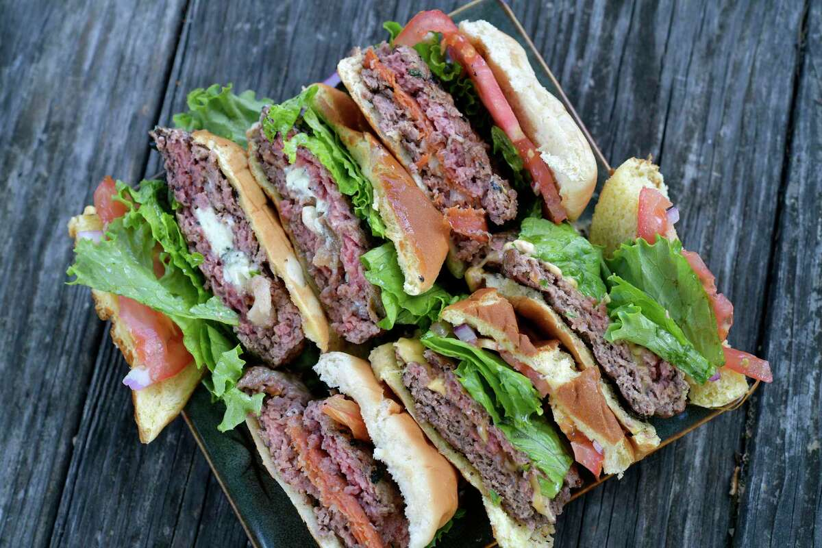 A lineup of stuffed burgers are finished off the grill.