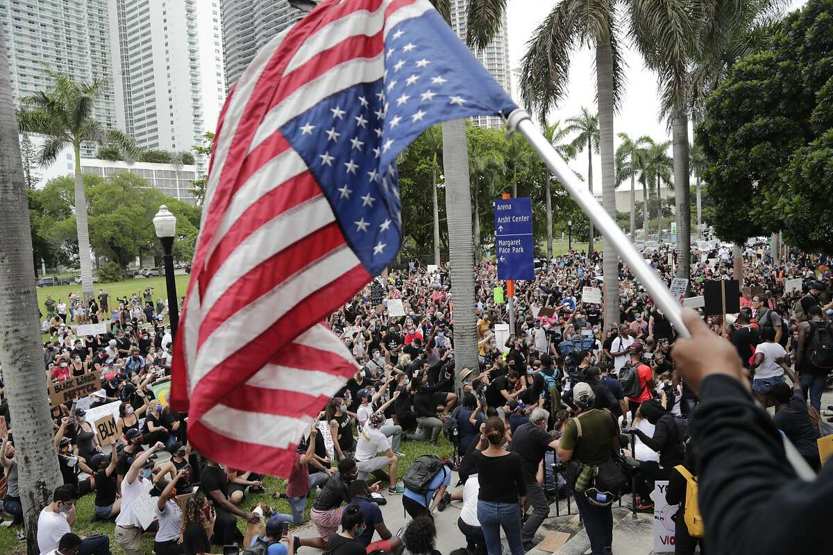 A protester holds the American flag upside down during a protest over the death of George Floyd, Saturday, June 6, 2020, in Miami. Protests continue over the death of Floyd, a black man who died while in police custody in Minneapolis. (AP Photo/Lynne Sladky)
