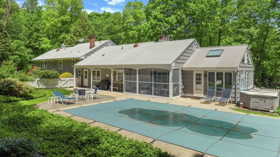This three-acre property has a covered porch, screened porch and open patio, all three looking over the heated in-ground swimming pool and hot tub.