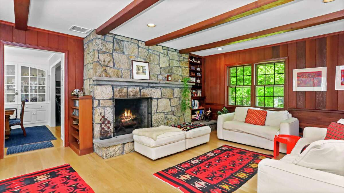 The family room has wood paneled walls, a floor-to-ceiling stone fireplace, exposed beams, and a door to the sun room.