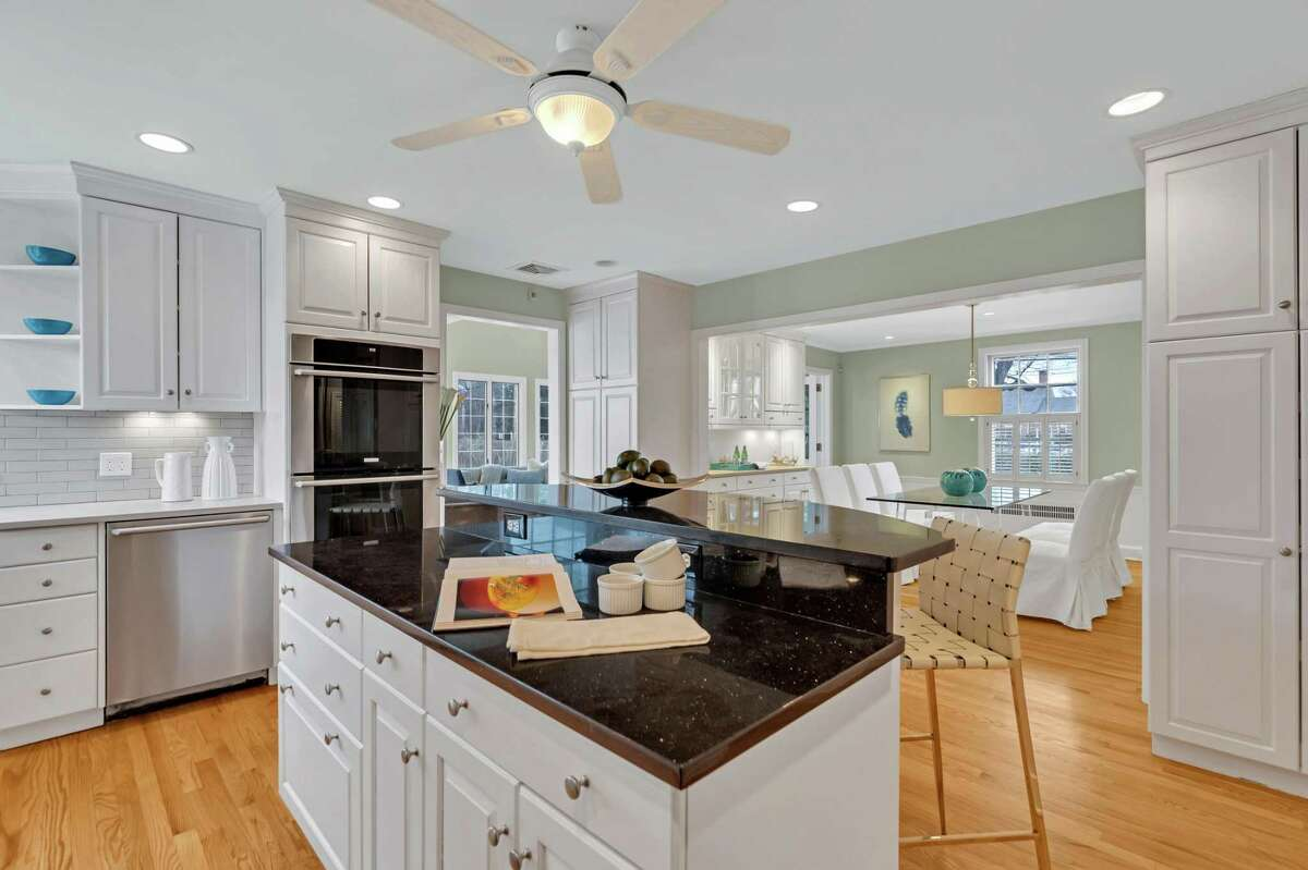 In the gourmet kitchen there is a two-tiered center island/breakfast bar, quartz counters, under cabinet lighting, a built-in wine rack and high-end stainless appliances. This house is