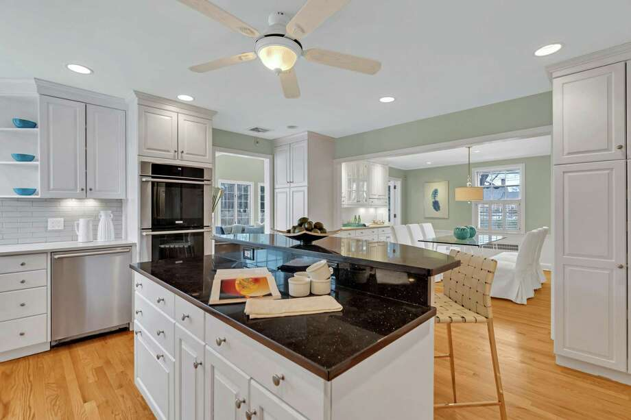 In the gourmet kitchen there is a two-tiered center island/breakfast bar, quartz counters, under cabinet lighting, a built-in wine rack and high-end stainless appliances.