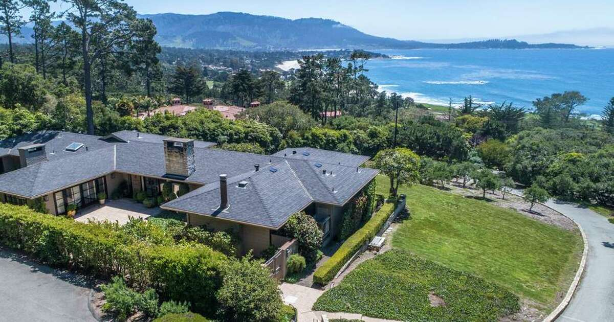 The Pebble Beach home features verdant gardens and views of the water.