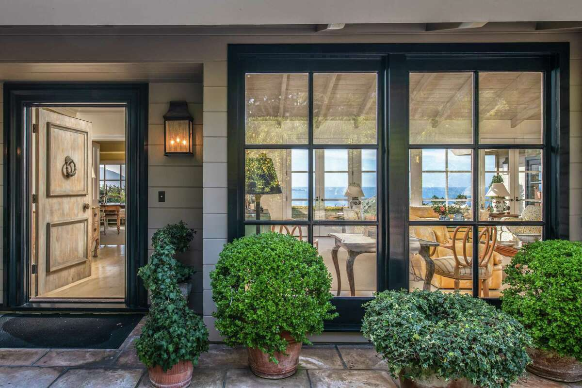 Multipane windows beside the front door overlook the garden of the Pebble Beach home.