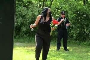 Ariel Owens walks away after handing a Plainfield police officer a rose Saturday during a rally near Plainfield Town Hall.