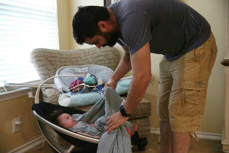 Brandon Beard takes his three-month-old son, Nolan, out of a rocker before a video call with his wife, Teresa, at their home May 21. She is working as a traveling nurse on an eight-week assignment at a hospital in Brooklyn.  At this point, she had two weeks left on her assignment.
