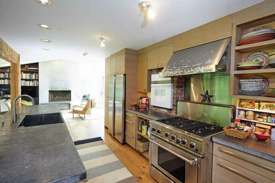In the kitchen there is a long center island and stainless steel appliances.