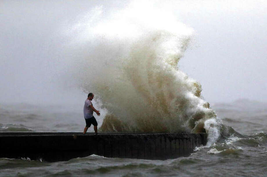 A wave crashes as a man stands on a jetty near Orleans Harbor in Lake Pontchartrain in New Orleans as Tropical Storm Cristobal approaches the Louisiana Coast. Photo: Gerald Herbert | AP