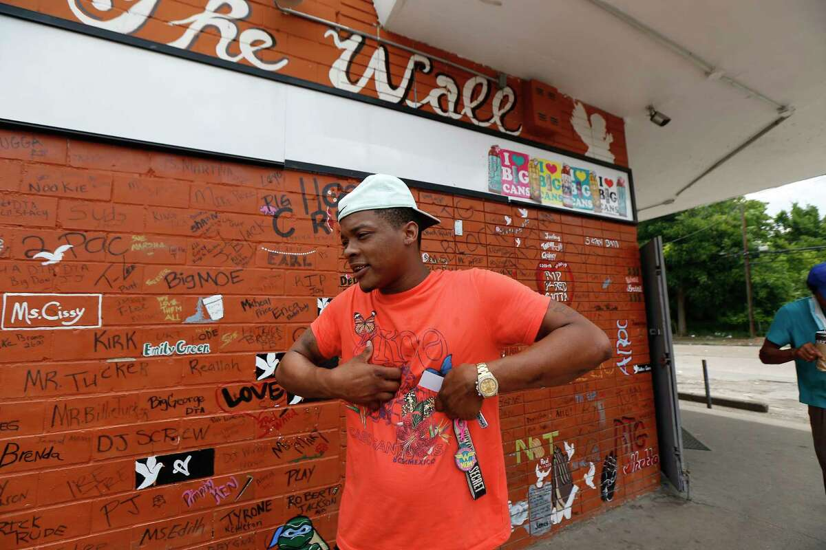 """Quo Taylor talks about """"The Wall"""" that honors neighbors who have died next to a mural made in honor of George Floyd outside the Scott Food Mart corner store in Houston's Third Ward. Monday, June 8, 2020, in Houston."""