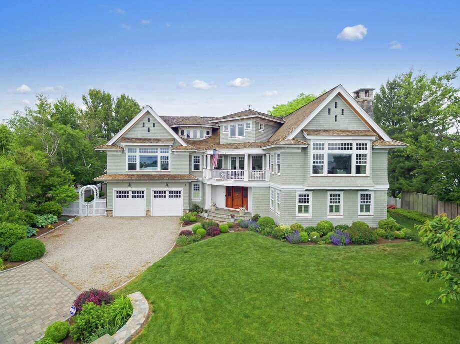 The gray shingle-style colonial house at 32 Surf Road in the Saugatuck Shores neighborhood provides waterfront living in a private, convenient setting.