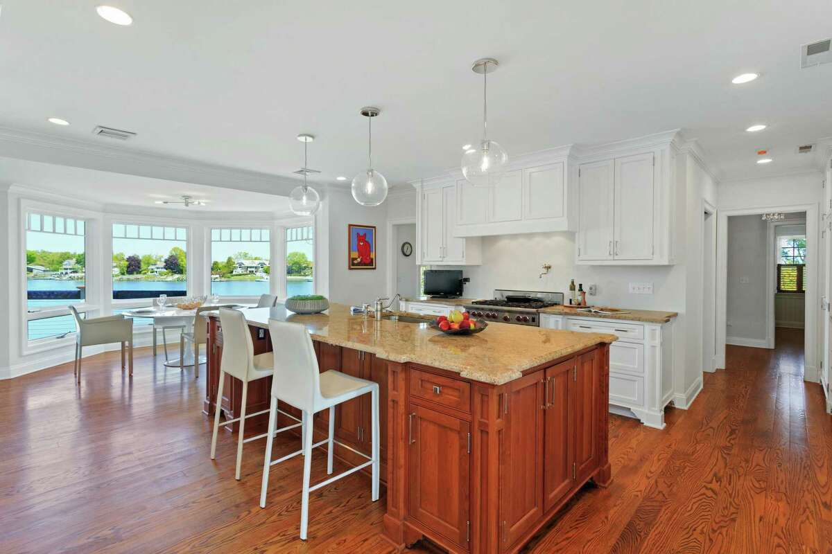 In the gourmet eat-in kitchen there is a long center island/breakfast bar, granite counters, breakfast nook with a door to a balcony, and stainless appliances.