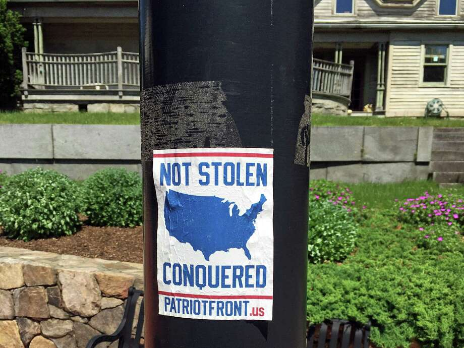 Stickers linked to a white nationalist group such as this one were removed from Sandy Hook light posts over the weekend and reported to police. Photo: Newtown Democratic Town Committee