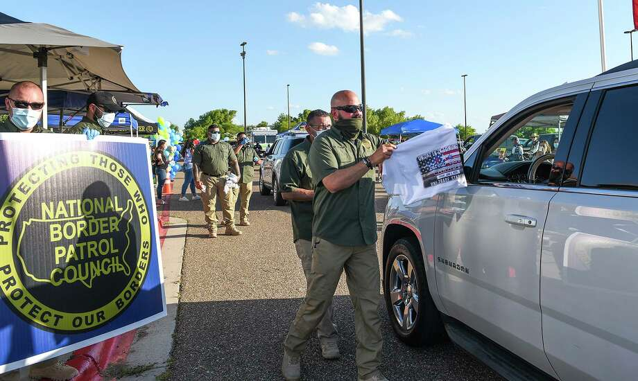 Members of the National Border Patrol Council handed out T-shirts to Laredoans as they drove by Friday, June 5 during the Laredo Unity Parade in Uni-Trade Stadium's parking lot. Photo: Danny Zaragoza /Laredo Morning Times