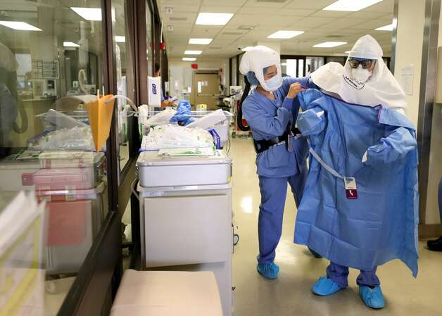 A nurse helps a doctor put on his personal protective equipment (PPE) before performing a procedure on a coronavirus patient. Photo: Justin Sullivan/Getty Images / 2020 Getty Images