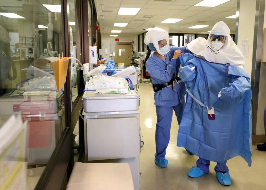 A nurse helps a doctor put on his personal protective equipment (PPE) before performing a procedure on a coronavirus COVID-19 patient in the intensive care unit (I.C.U.) at Regional Medical Center on May 21, 2020 in San Jose, California. Frontline workers are continuing to care for coronavirus COVID-19 patients throughout the San Francisco Bay Area. Santa Clara county, where this hospital is located, has had the most deaths of any Northern California county, and the earliest known COVID-19 related deaths in the United States.