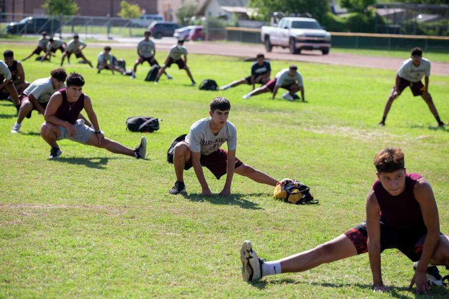 Players stretch spaced out on the field during the first day of strength and conditioning camp at Harlandale High School San Antonio, Texas, on June 8, 2020. The camp looked different than past years as players maintained social distance from one another, minimal contact in drills and weight equipment was sanitized after each use. Photo: Josie Norris, The San Antonio Express-News / Staff Photographer / **MANDATORY CREDIT FOR PHOTOG AND SAN ANTONIO EXPRESS-NEWS/NO SALES/MAGS OUT/TV