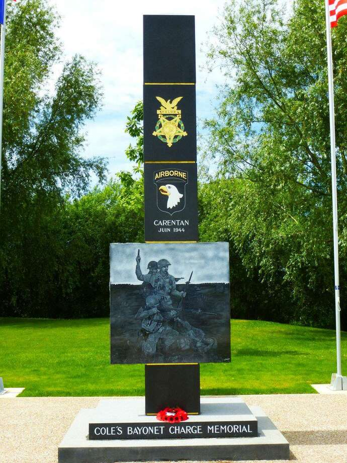 A dark stone monolith with an engraved Medal of Honor and the 101st Airborne Unit insignia is at the spot in France where Lt. Col. Robert Cole led his battalion in a bayonet charge after being hopelessly pinned down to drive back the enemy and secure the approach to Carentan. Cole was awarded the Medal of Honor for his actions here. Photo: Contributed Photo / Wilton Bulletin