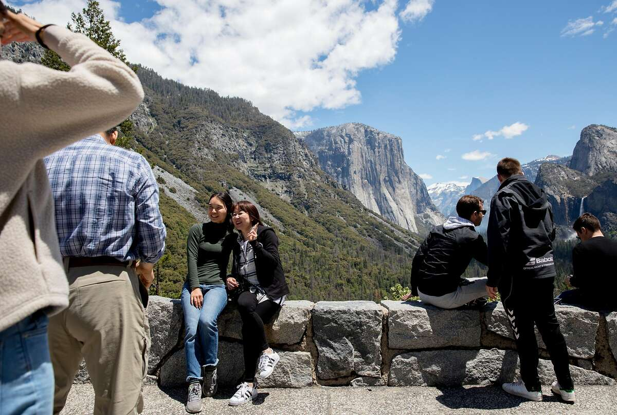 Tourists take pictures at the Tunnel View vista point inside Yosemite National Park in Yosemite, Calif. Tuesday, May 28, 2019.