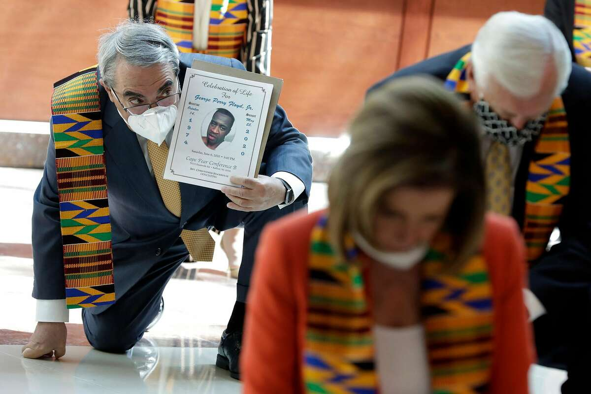 Congressman G. K. Butterfield (D-N.C.) holds a portrait of George Floyd behind U.S. House Speaker Nancy Pelosi (D-Calif.) as Congressional Democrats observe moment of silence for eight minutes and 46 seconds to honor George Floyd, Breonna Taylor, Ahmaud Arbery and others, on Monday, June 8, 2020 on Capitol Hill in Washington, D.C. (Yuri Gripas/Abaca Press/TNS)