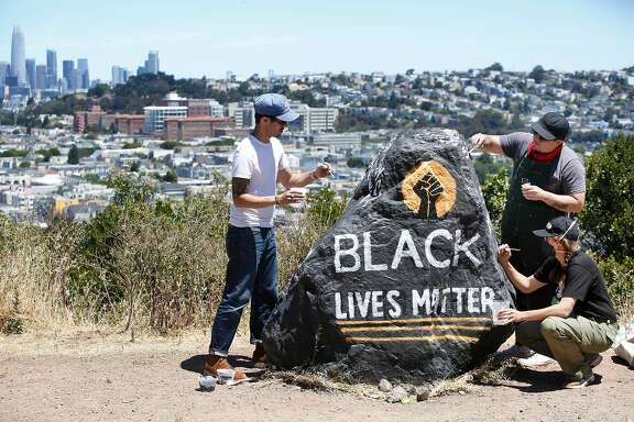 Kseniya Makarova (right front); Micah Rivera (right back) and Manny Fabregas (left), all of San Francisco, paint a rock on Folsom Street for Black Lives Matter on Monday, June 8, 2020 in San Francisco, Calif. Makarova painted the rock for the for the first time last Wednesday and had to repaint it after it was covered with spray paint. Today is the fifth time she is repainting it.