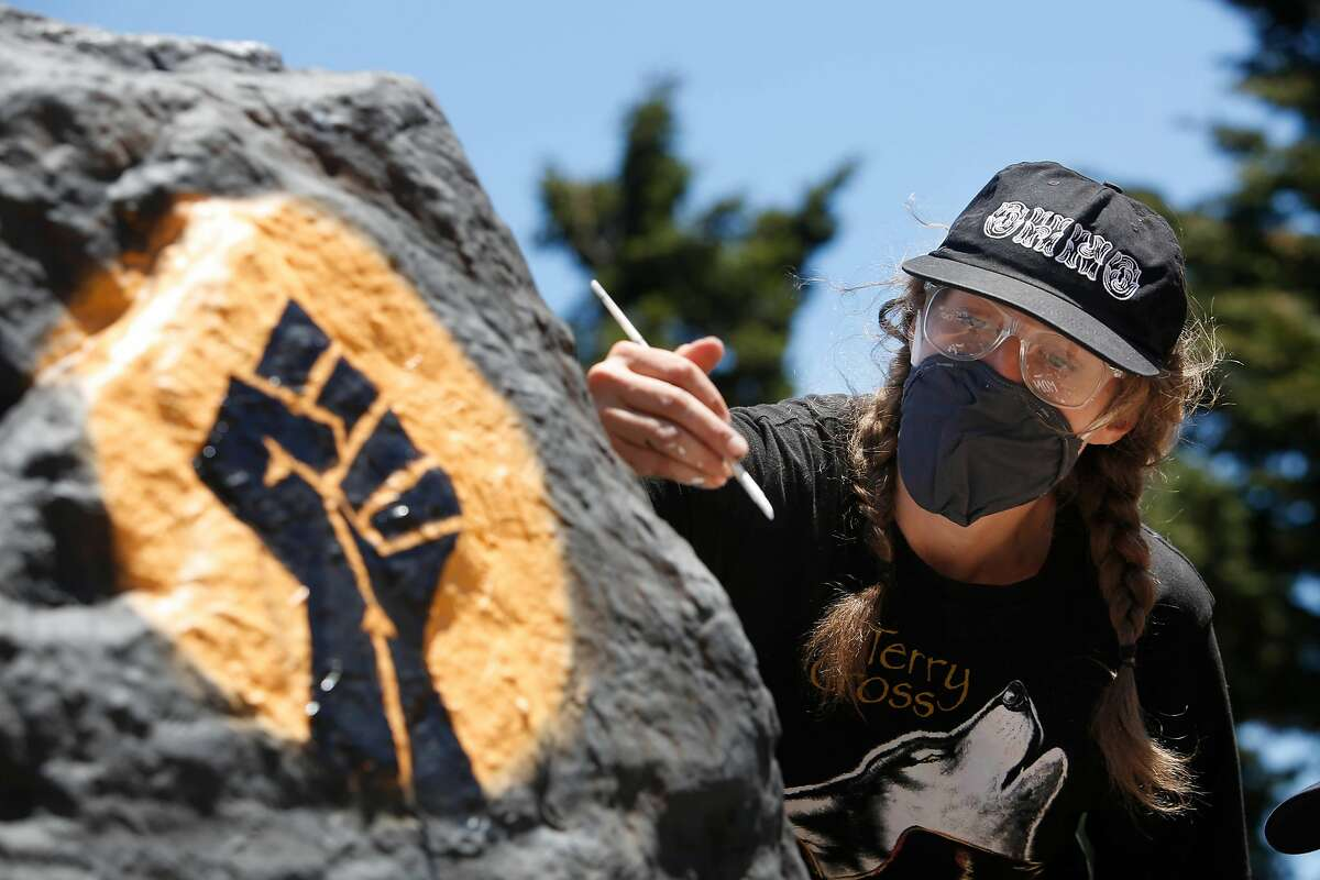 Kseniya Makarova, of San Francisco, paints a rock on Folsom Street for Black Lives Matter for the fifth time in less than a week on Monday, June 8, 2020 in San Francisco, Calif. Makarova painted the rock for the for the first time last Wednesday and had to repaint it after it was covered with spray paint. Today is the fifth time she is repainting it.